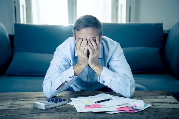 住宅ローンの返済ができず頭を抱えている男性